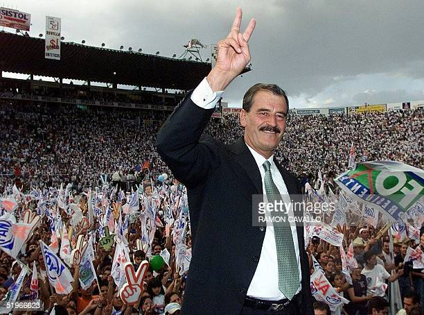 Mexican presidential candidate Vicente Fox of the conservative National Action Party flashes a peace sign like that of his supporters in Guanajuato...