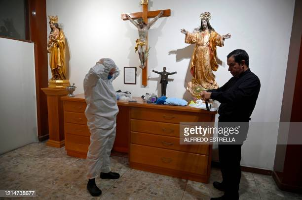 Mexican priest Andres Esteban Lopez is helped by priest Roberto Funes put protective gear on to go to the General Hospital, at the Sagrada Familia...