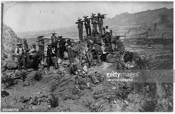 A Mexican rebel group aims and shoots from a boulder overlooking a desert valley with factories Mexico