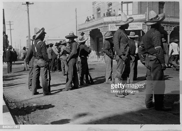 Mexican rebels carrying rifles stand in the streets of Juarez after the government surrenders Chihuahua Mexico