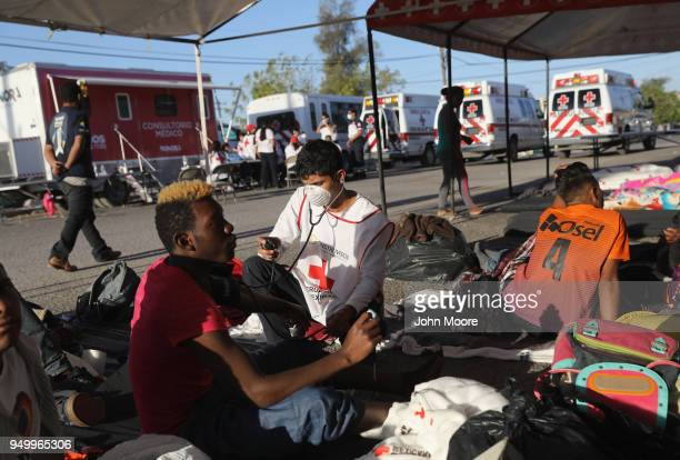 Mexican Red Cross worker checks an immigrant's blood pressure during a pause on the journey towards the USMexico border on April 22 2018 in...