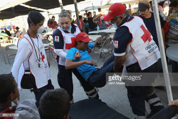 Mexican Red Cross workers carry a sick immigrant to an ambulance at a shelter on April 22 2018 in Hermosillo Mexico Some 600 immigrants part of a...