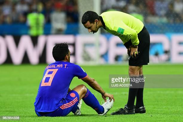 Mexican referee Cesar Ramos talks to Colombia's midfielder Abel Aguilar after an injury during the Russia 2018 World Cup Group H football match...