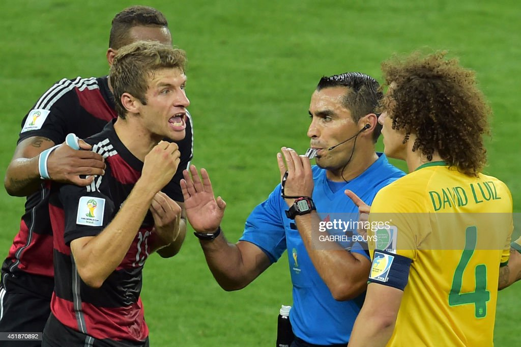 Mexican referee Marco Rodriguez stands in between Brazil's defender David Luiz (R) and Germany's forward Thomas Mueller (L) arguing during the semi-final football match between Brazil and Germany at The Mineirao Stadium in Belo Horizonte during the 2014 FIFA World Cup on July 8, 2014.