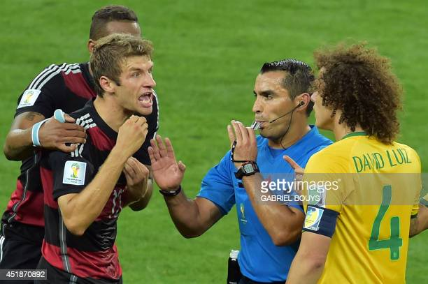 Mexican referee Marco Rodriguez stands in between Brazil's defender David Luiz and Germany's forward Thomas Mueller arguing during the semifinal...