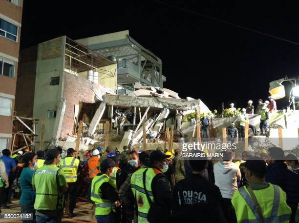 Mexican rescue teams look for people trapped in the rubble at the Enrique Rebsamen elementary school in Mexico City on September 19 2017 At least 21...