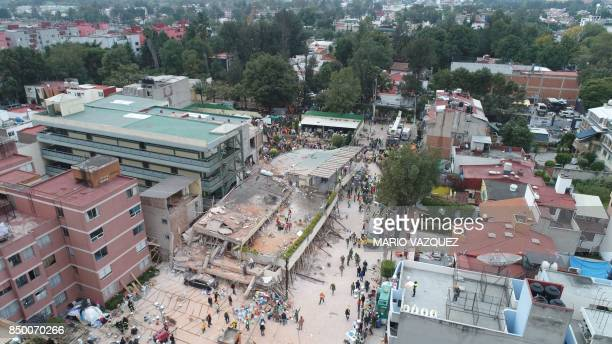 Mexican rescue teams look for people trapped in the rubble at the Enrique Rebsamen elementary school in Mexico City on September 20 2017 At least 21...