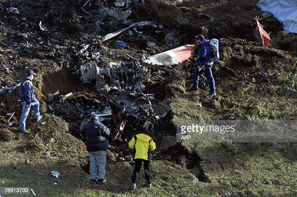 Mexican rescuers look at the remains of a helicopter crashed on Tepango de Rodriguez community in Puebla State Mexico 11 January 2008 The accident...