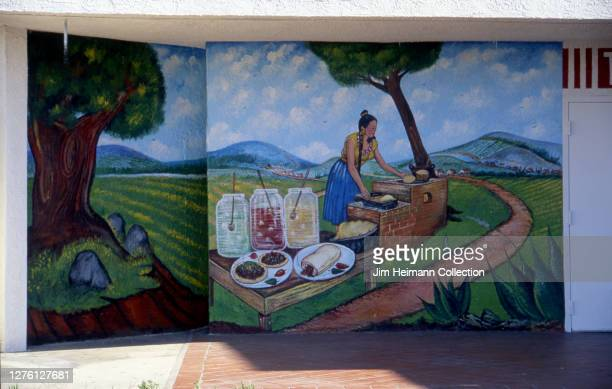 A Mexican restaurant in Los Angeles California has a mural of a woman making tortillas in the countryside painted on the wall 1997