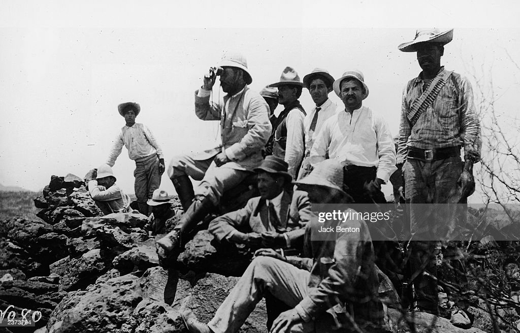 Mexican revolutionary leader Pancho Villa (1878 - 1923) looks through a set of binoculars, surrounded by his men, 1910s.