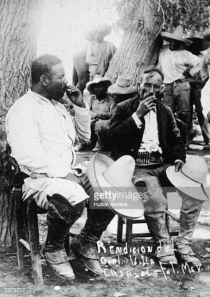 Mexican revolutionary leader Pancho Villa sits against a tree with a fellow soldier their straw hats over their knees following the Mexican...