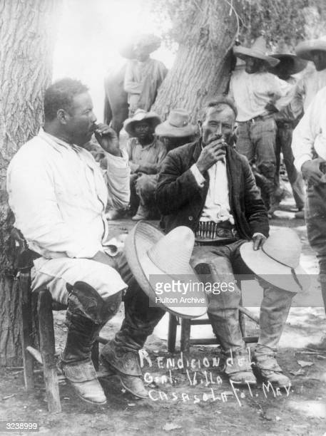 Mexican Revolutionaries Pancho Villa and Emiliano Zapata smoke cigarettes while sitting outdoors in front of bandits Mexico