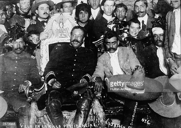Mexican revolutionary leaders Emiliano Zapata and Pancho Villa sit in front of a group of soldiers January 2 1915
