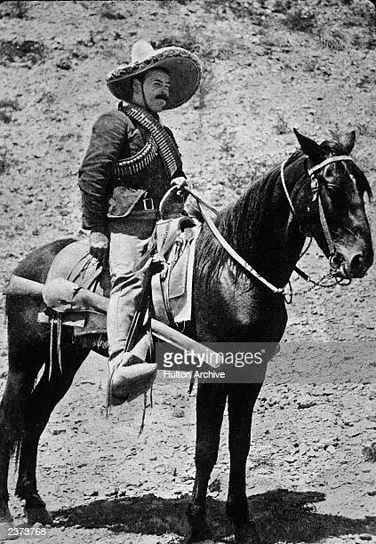 Mexican revolutionary Pancho Villa sits on horseback wearing a straw hat and ammunition strapped across his shoulders 1910s