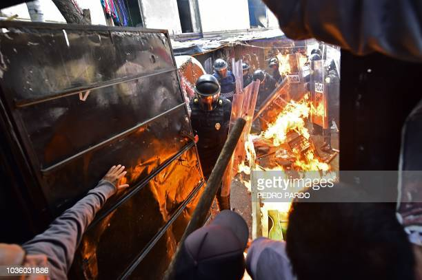 TOPSHOT Mexican riot police clash with residents of an indigenous camp as they are evicted from the improvised homes where many had been living for...