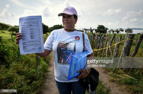 Mexican Rosa Lopez mother of missing Jose Damian Guzman show documents of the local attorney's office as she waits on September 17 to enter the site...
