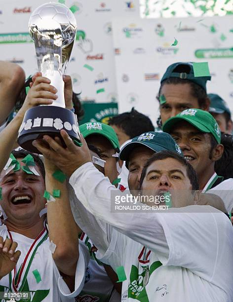 Mexican Santos' coach Daniel Guzman holds the trophy with teammates after winning the Mexican football league tournament in Torreon state of Coahuila...