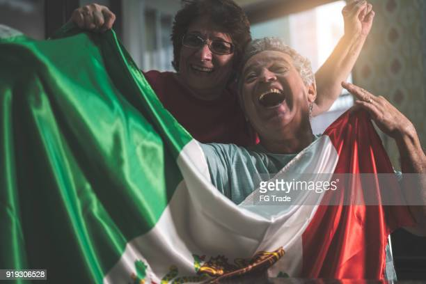 mexican senior couple fan watching soccer game at home - mexican flag stock pictures, royalty-free photos & images