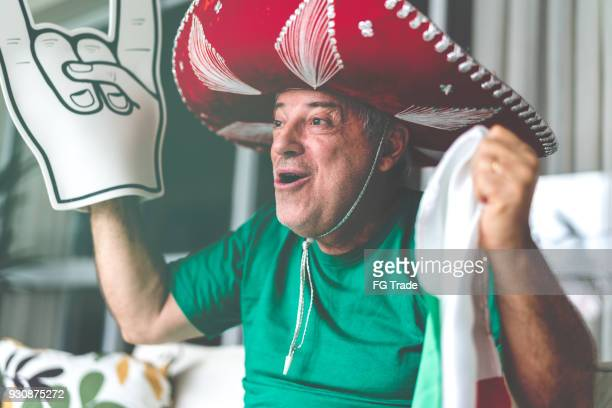 Mexican senior fan watching soccer game at home