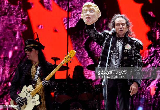 Mexican singer and composer Alex Lora of the band El Tri shows a mask of US President Donald Trump as he performs during the second day of the Vive...