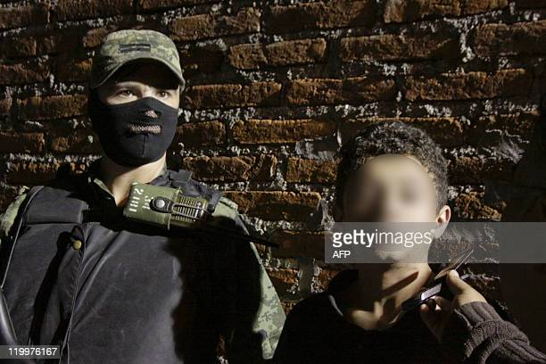 A Mexican soldier escorts Edgar Jimenez Lugo aka 'El Ponchis' alleged member of the South Pacific drug cartel in Cuernavaca Morelos State Mexico on...