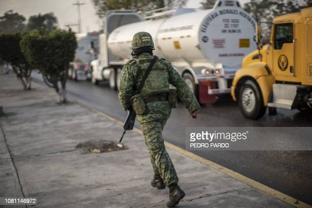 A Mexican soldier guards the entrance to an oil refinery of Mexico's oil company PEMEX where private tanker trucks are being supplied with fuel in...