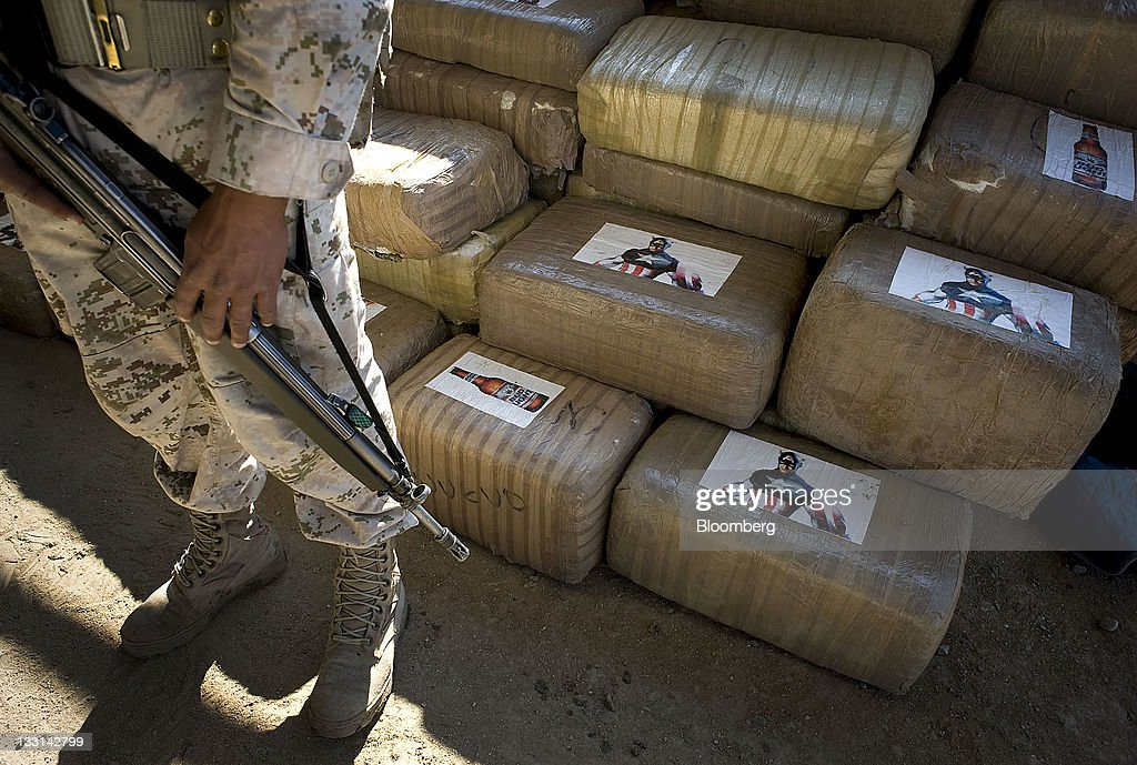 A Mexican soldier stands guard next to packages of marijuana found at a warehouse in Tijuana, Mexico, on Wednesday, Nov. 16, 2011. Approximately 17 tons of marijuana were discovered in a cross-border tunnel that appears to be one of the most significant drug smuggling passages found between the U.S. and Mexico. Photographer: David Maung/Bloomberg via Getty Images
