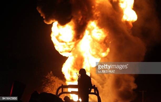 Mexican soldier stands guard while workers of the Mexican state-owned oil company Pemex and local firefighters work to control a fire believed to...