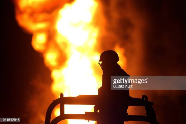 A Mexican soldier stands guard while workers of the Mexican stateowned oil company Pemex and local firefighters work to control a fire believed to...