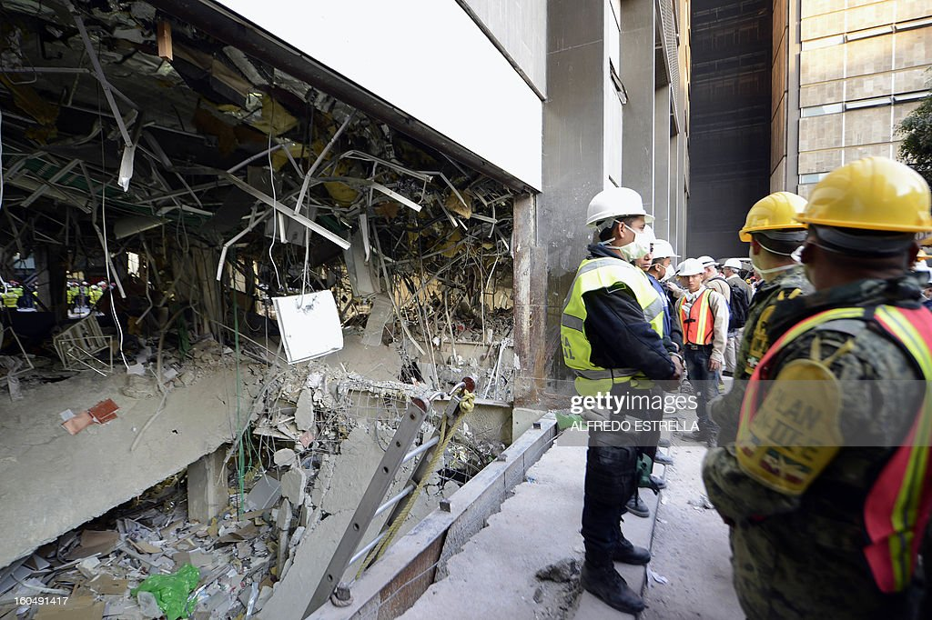 Mexican soldiers and Federal policemen stand guard next to the damaged building of state-owned Mexican oil giant Pemex, following a blast on the eve, in Mexico City on February 1, 2013. An explosion rocked the skyscraper, leaving up to 32 dead and 121 injured. Hundreds of firefighters, police and soldiers toiled through the night after the blast ripped through an annex of the 54-floor tower leaving concrete, computers and office furniture strewn on the ground. AFP PHOTO/Alredo Estrella