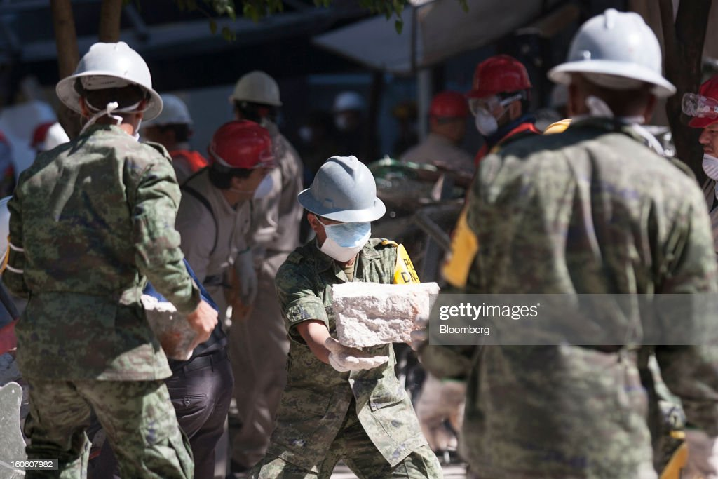 Mexican soldiers clean up debris at the Petroleos Mexicanos (Pemex) administrative building in Mexico City, Mexico, on Sunday, Feb. 3, 2013. The search for the cause of a blast that destroyed three floors of a building at Pemex' headquarters and killed at least 34 people entered a fourth day, as investigators toiled ahead of a self-imposed deadline for finding an answer. Photographer: Susana Gonzalez/Bloomberg via Getty Images