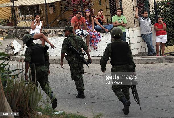 Mexican soldiers near at the site of a suspected drug execution on February 28, 2012 in Acapulco, Mexico. Drug violence surged in the coastal resort...