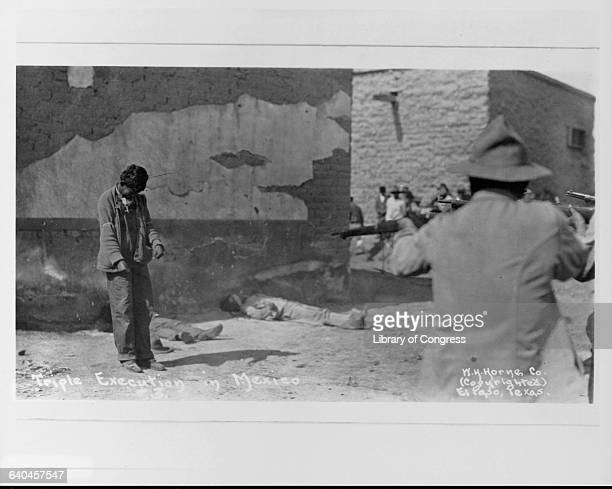 Mexican soldiers shoot three rebels on the street of a town in an execution during the Mexican Revolution