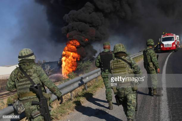 Mexican soldiers stand guard next to flames caused by the explosion of a gas pipeline in Zapopan Jalisco State Mexico on February 14 2017 / AFP / STR