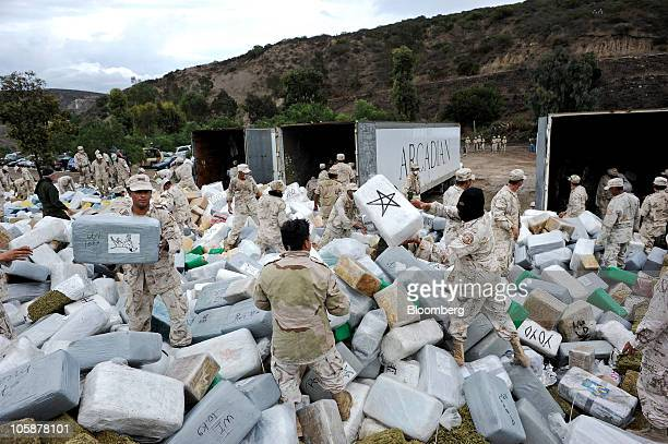 Mexican soldiers unload bundles of seized marijuana before incinerating the drugs at a military base in Tijuana, Mexico, on Wednesday, Oct. 20, 2010....
