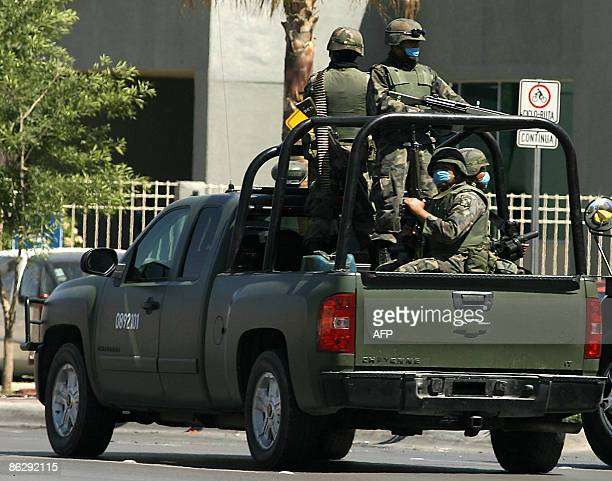 Mexican soldiers wearing surgical masks patrol a street on April 29 2009 in Juarez Mexico The World Health Organisation raised its flu alert to phase...