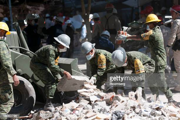 Mexican soldiers wearing the identification of Plan DNIIIE clean up debris at the Petroleos Mexicanos administrative building in Mexico City Mexico...