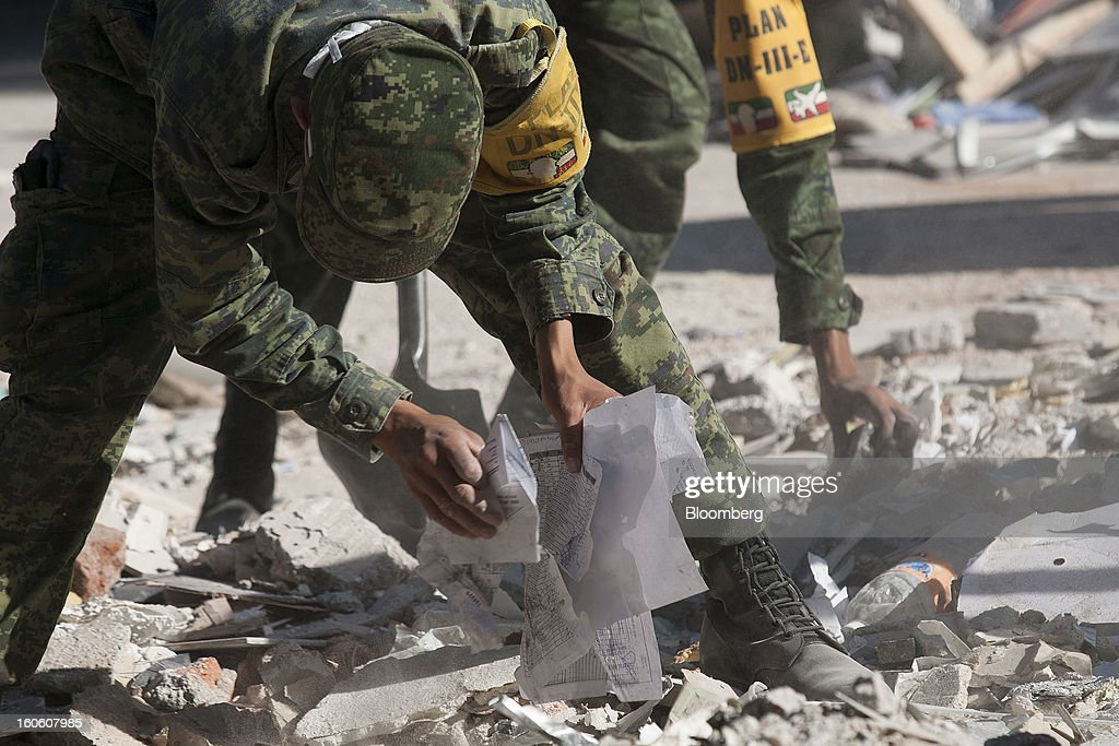 Mexican soldiers, wearing the identification of Plan DN-III-E, clean up debris and recover administrative documents at the Petroleos Mexicanos (Pemex) administrative building in Mexico City, Mexico, on Sunday, Feb. 3, 2013. The search for the cause of a blast that destroyed three floors of a building at Pemex' headquarters and killed at least 34 people entered a fourth day, as investigators toiled ahead of a self-imposed deadline for finding an answer. Photographer: Susana Gonzalez/Bloomberg via Getty Images