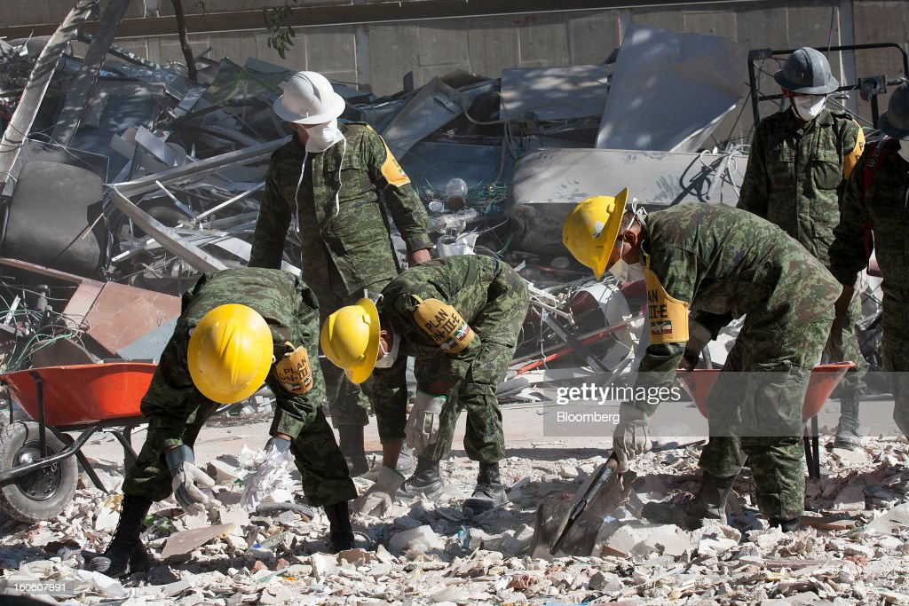 Mexican soldiers, wearing the identification of Plan DN-III-E, clean up debris at the Petroleos Mexicanos (Pemex) administrative building in Mexico City, Mexico, on Sunday, Feb. 3, 2013. The search for the cause of a blast that destroyed three floors of a building at Pemex' headquarters and killed at least 34 people entered a fourth day, as investigators toiled ahead of a self-imposed deadline for finding an answer. Photographer: Susana Gonzalez/Bloomberg via Getty Images