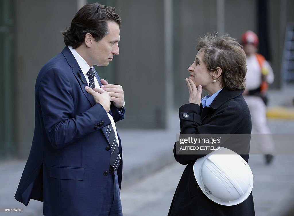 Mexican state-owned oil giant Pemex's Chief Executive Officer, Emilio Lozoya (L) talks with Mexican journalist Carmen Aristegui (R) outside the damaged building of the company, after a blast, in Mexico City on February 5, 2013. A gas build-up caused the explosion that rocked the headquarters of Mexico's state-owned oil firm last week, killing 37 people, officials said Monday, ruling out a bomb attack. The explosion also injured morfe than 120 people. AFP PHOTO/Alredo Estrella