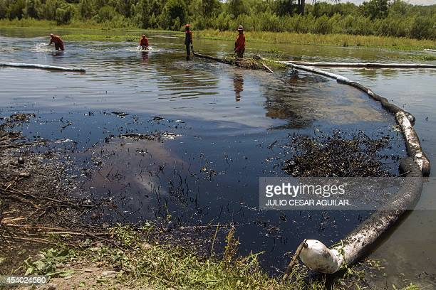Mexican stateowned petroleum company Pemex's workers clean the San Juan river after an oil spill caused by a clandestine taking in a pipeline in San...