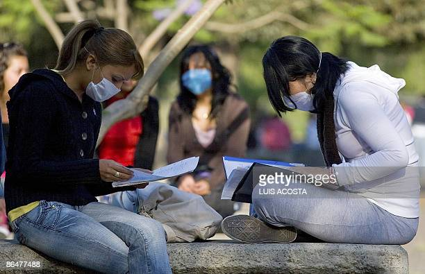 Mexican students read some notes while they wear surgical masks at the Faculty of Medicine in the Mexican Autonomous University in Mexico City on May...