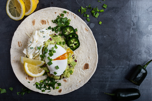 Mexican style breakfast with poached egg, guacamole and coleslaw on flour tortilla - gettyimageskorea