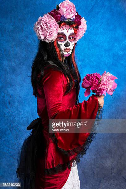 Mexican sugarskull bride, three quarter length looking at camera.