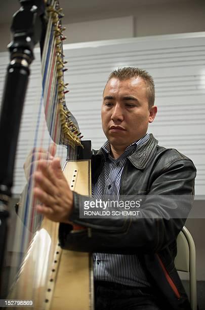 Mexican teacher Jonas Barrera plays his harp berfore an entrance examination at Ollin Yolitzli mariachi music school at the Garibaldi square in...