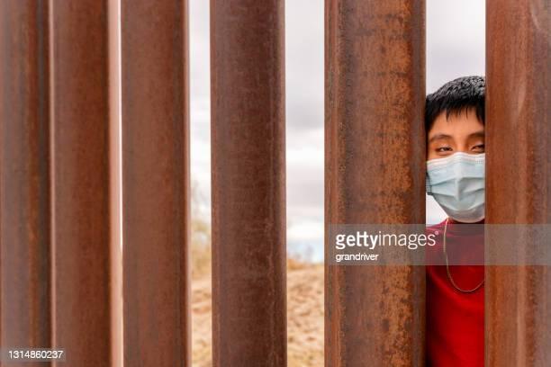 彼らは米国とメキシコの間の国際国境障壁の壁のスラットの間を見てcovid-19マスクを身に着けているメキシコの十代の少年 - メキシコ北部 ストックフォトと画像