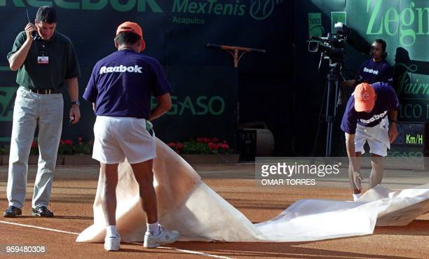 Mexican Tennis Open staff repair the central court after the match between Brazilian players Gustavo Kuerten and Fernando Meligeni was suspended 02...