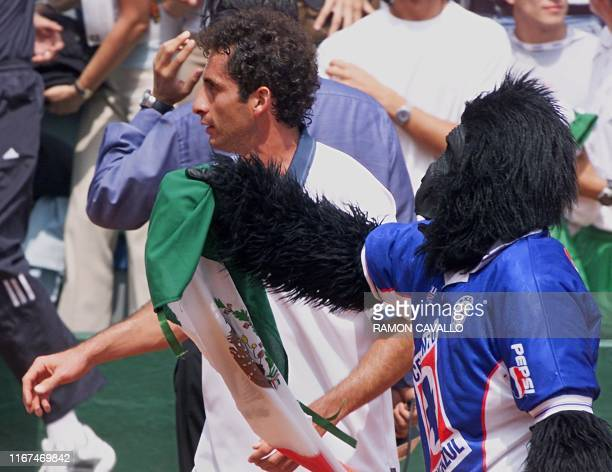 Mexican tennis player Alejandro Hernandez is greeted by a flagbearing fan in a gorilla costume as he celebrates his Davis Cup victory over F Niemeyer...