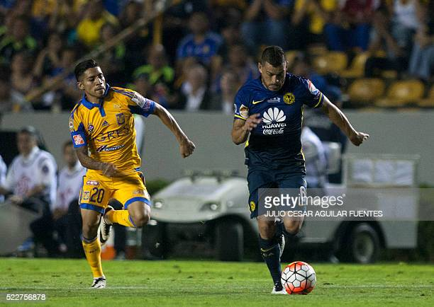 Mexican Tigres' player Javier Aquino vies for the ball with Miguel Samudio of Mexico's America during the firs leg of the final of the Concacaf...