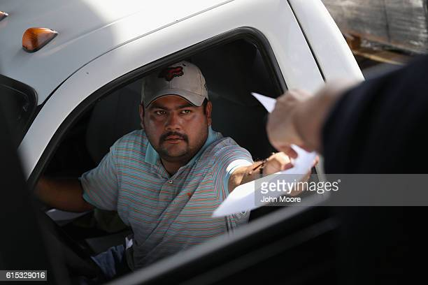Mexican trucker hands over manifest documents to a US Customs and Border Protection officer on October 17 2016 in Laredo Texas South Texas customs...
